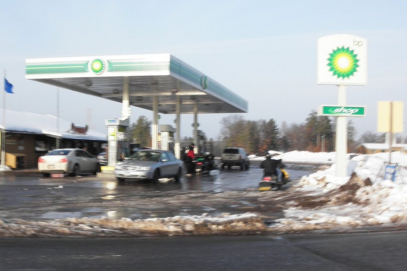 Snowmobiles filling up at the gas station