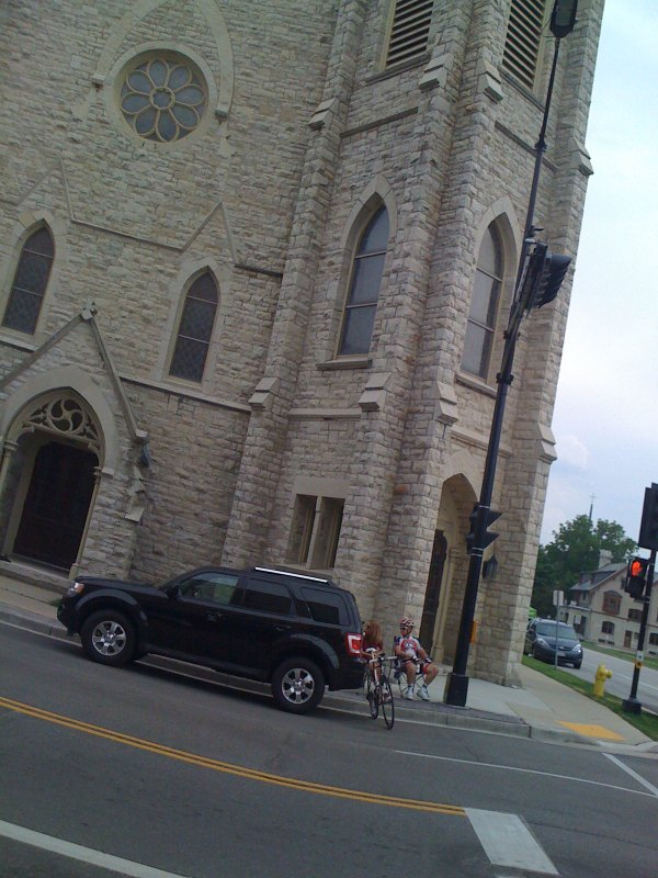 Bike racer parked in front of a different church