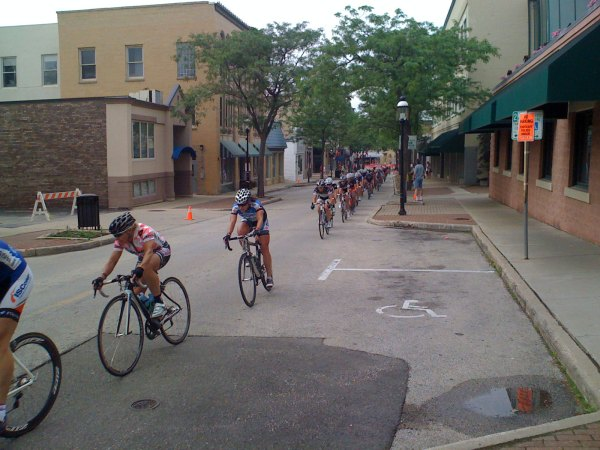 The pro women's field is strung out coming up the hill between turns 1 and 2
