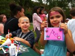 Analise and Josiah make bicycle tags at a festival on the course