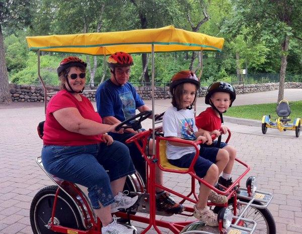 Grandma Sandy and Poppa Dale pedal the kids around the park