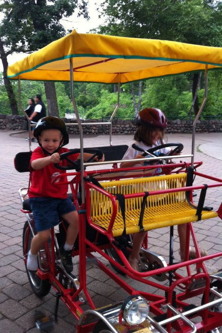 The kids try pedaling on their own -- it looks like Josiah has lost a shoe.