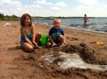 Analise and Josiah using good teamwork to build sand castles.