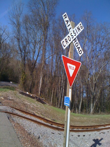 """For some reason I found this yield sign at the train tracks funny and ironic. I guess they realized that nobody would stop at a stop sign so they changed it to a yield sign to remind you that the train has the right-of-way? It reminded me of the sign you sometimes see at airports """"yield to airplanes""""."""