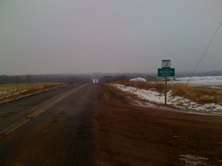More of Co Rd J with blowing snow in the distance