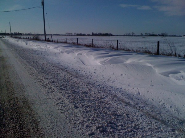 Slushy road and huge snow drifts - can you tell which way the wind is blowing from?