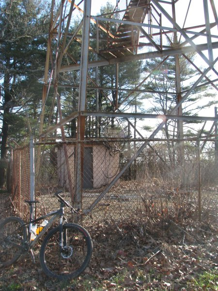 My bike at the base of the fire tower with barbed wire fence and missing bottom steps