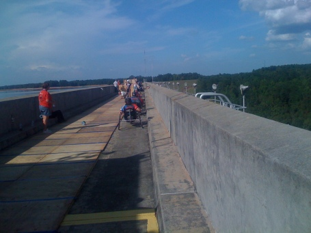 Handcyclists pass over the dam in the narrow space between the planks and the wall