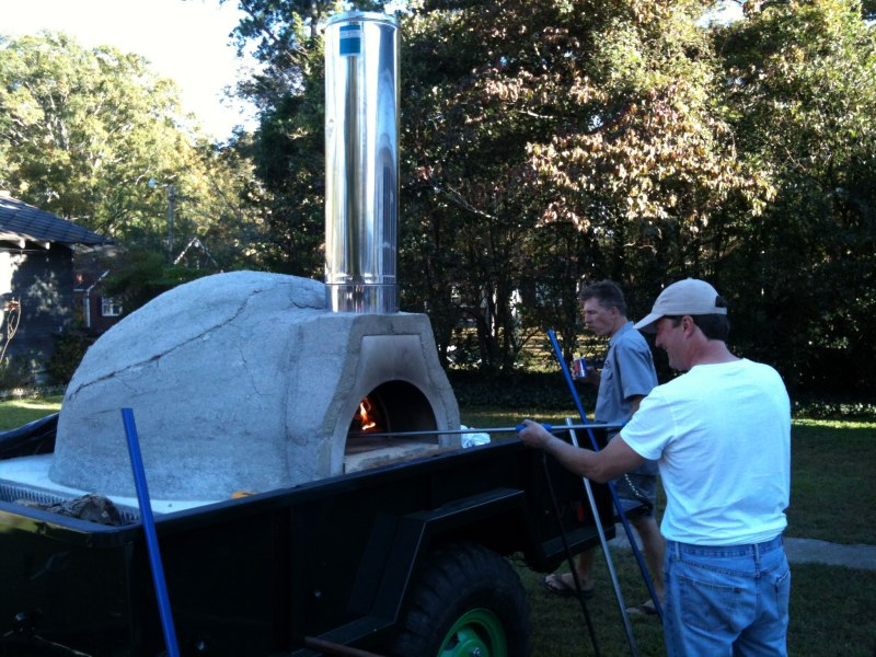 Bill St John cooks delicious pizzas in his portable stone oven.