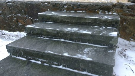 Tues, 1/28 @ 10:41AM - icy fall. Trying to get down to a platform for a better view of the fire damage, I step down onto these steps without examining them closely. As soon as my foot hits the top step, it slips out from under me. As if in a cartoon, I slide all the way down to the bottom. These steps are coated with about 1/4 inch of solid, clear, smooth ice from the firefighting the night before and then the strong north wind all night and all morning.
