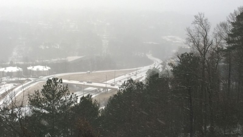 Tues 1/28 @ 10:43AM - hwy 31 starting to stall. Even at this point only an hour or so after the snow first started to fall, cars are struggling to get up Hwy 31. You can see a pileup at the sharp bend at the bottom and a shuttle bus off the side of the steep exit ramp. Also, the second cars heading up the hill are moving (I have a sequence of pictures showing them in different positions) but the first car is turned sideways from starting to spin out.