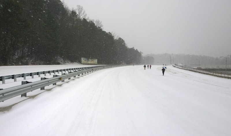 People walk down a completely empty three lane highway about 3 hours after it first started to snow