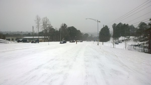 Tues, 1/28 @ 1:57PM - US Hwy 31 at the library. A little farther down the hill, I see a man walking down Hwy 31 south at the Vestavia Hills Library. Cars have slid into the grassy median. I start to worry about my own traction as the road is starting to get icy. I pick my route more carefully alternating between riding in the grass or deeper snow on the road depending on which looks faster and easier to ride. Wind-blown stretches like the one shown in this picture had to be avoided. You can see in this picture that I am riding down a stretch of deeper snow between two wind-blown sections.