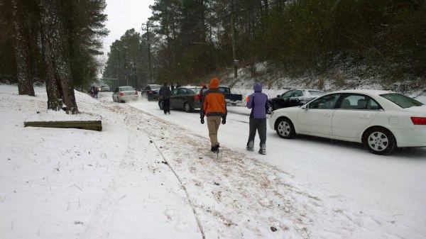 Tues, 1/28 @ 2:25PM - rocky ridge rd wisteria hill. I stop on Rocky Ridge Rd looking back up the hill. These people have given up and are walking towards home. Abandoned cars are off the road in a small ditch on the right, other cars still try to make it on the left. Cars line up behind at the top of the hill waiting to see what happens.