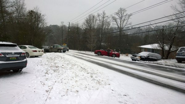 Tues, 1/28 @ 2:29PM - crash on rocky ridge rd. I cross the road between these cars that have spun off opposite sides of the road. Judging by minor front-end damage, it looks like they may have hit each other head on at very slow speed. Other cars are stuck behind. All cars visible in this picture should not be there, i.e., the house on the left and the house on the right do not normally have cars parked in their front yards. People may have abandoned these cars and started walking home.