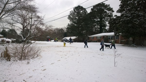 Tues 1/28 @ 2:58PM - walking home from school. Kristine walks in the middle of a group of kids walking home from school. The kids are happy as clams to be playing in the snow. Another parent walks with his dog towards school to pick up their kids.