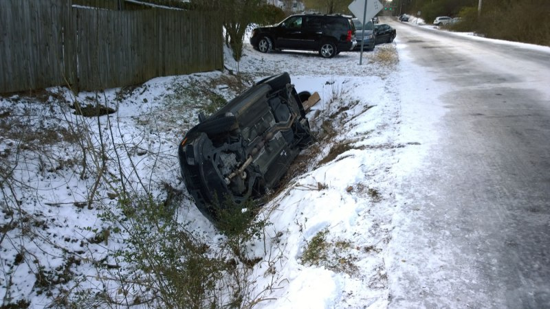 Wed, 1/29 @ 8:03AM - first flipped car. I only have to ride 1/2 mile from my house to stumble (almost literally) upon the first flipped car. Rocky Ridge Rd was so icy that I walk stretches of it. I am trying to ride down the middle of the road where there is a little bit of snow (and traction), but graviity pulls me across to the side of the road onto the shoulder where I am completely shocked to be staring at this car in front of me. This moment is recorded 7 minutes and 50 seconds into this video: http://youtu.be/31u73UqPQ4A. I park my bike alongside the sign and run down to the car just to make sure nobody is still in the car (i.e., in case it had just happened while I was biking down the other side of the hill). Nobody is inside, but the contents of the car are strewn everywhere.