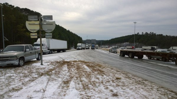 Wed, 1/29 @ 10:36AM - tractor trailer ice skating. None of the tractor trailers in this picture of the I-459 interchange are moving. The stuff you see on the roads is crazy slippery ice, impossible to ride or walk on. We have to navigate carefully to get to this point. This is the first picture I take after we spend nearly an hour between Old Rocky Ridge Rd and this spot handing out food, talking to people who have been in their cars and trucks for close to 24 hours, and letting them borrow our cellphones to make phone calls. A dollar general truck tries unsuccessfully to make it up the ramp here: http://youtu.be/Ufsg825mdtM