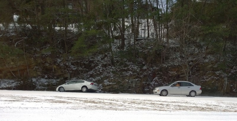 Wed, 1/29 @ 11:48AM - chains work. We see this car several times and observe that he must be shuttling people up and down the Columbiana hill with chains installed on his front-wheel drive wheels. Here he passes another four-door sedan that has slid off the road into a ditch so very close to the top of the hill.