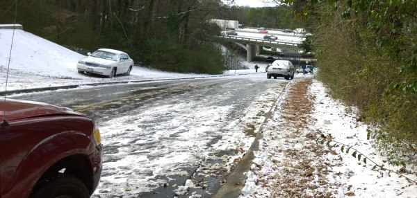 Wed, 1/29 @ 12:02PM - forest brook hill. We stare down at carnage at the bottom of this 16% hill that goes under I-65. The top is melting a bit, but from about halfway down to the bottom, it is a solid sheet of ice.