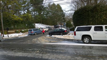Wed, 1/29 @ 2:32PM - countrywood neighborhood entrance. Cars litter the side of the countrywood neighborhood entrance hill. The hill looks like it has melted a good bit, but people haven't made it back to get their cars yet.