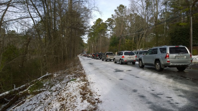 Wed, 1/29 @ 2:32PM - rocky ridge rd at countrywood. Cars queue to attempt to climb the icy hill one at a time. We have just come down the opposite side, forced to ride in the grass because the ice is unrideable through here. Just past this stretch, though, the sun has completely melted the ice away and we splash through lots of cold water on our way to the grocery store to pick up more food.